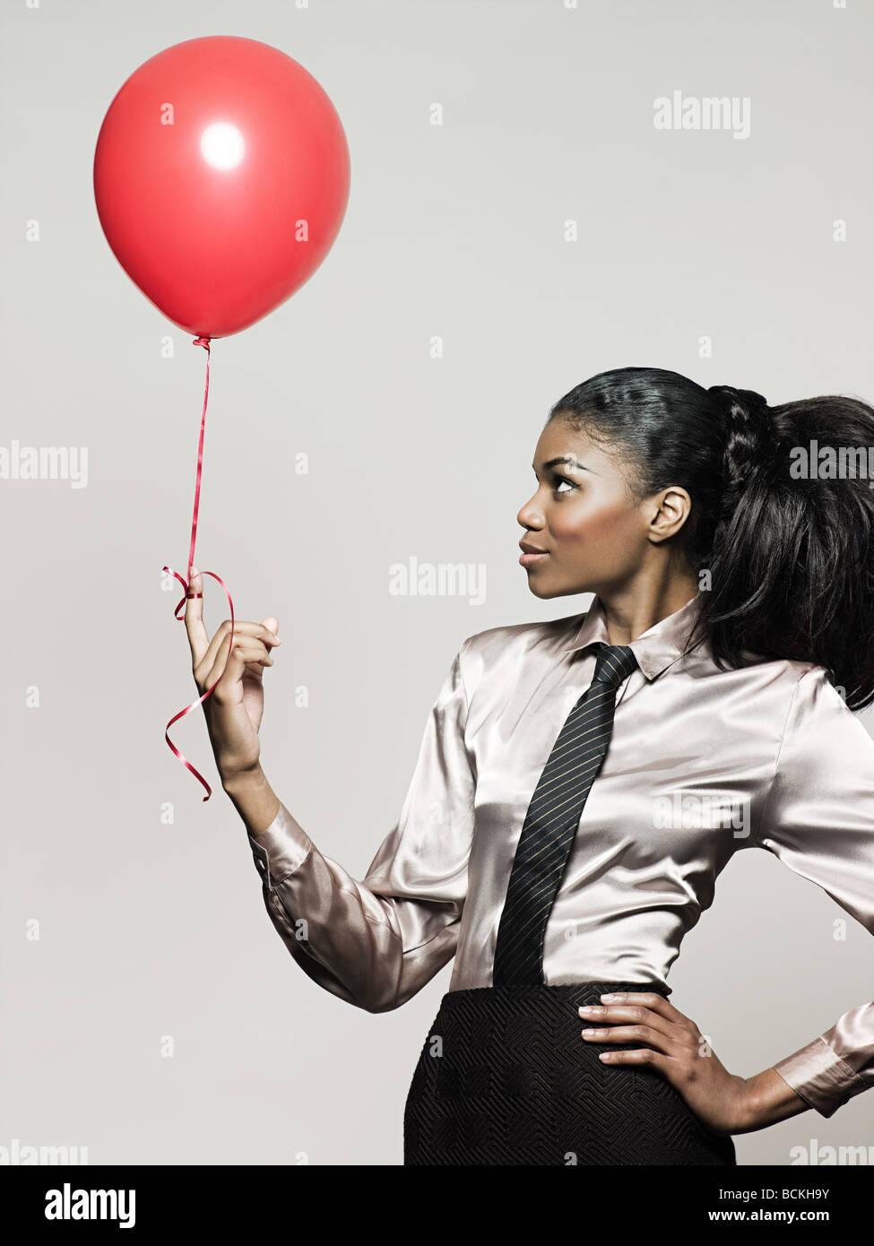 Businesswoman holding balloon - Stock Image