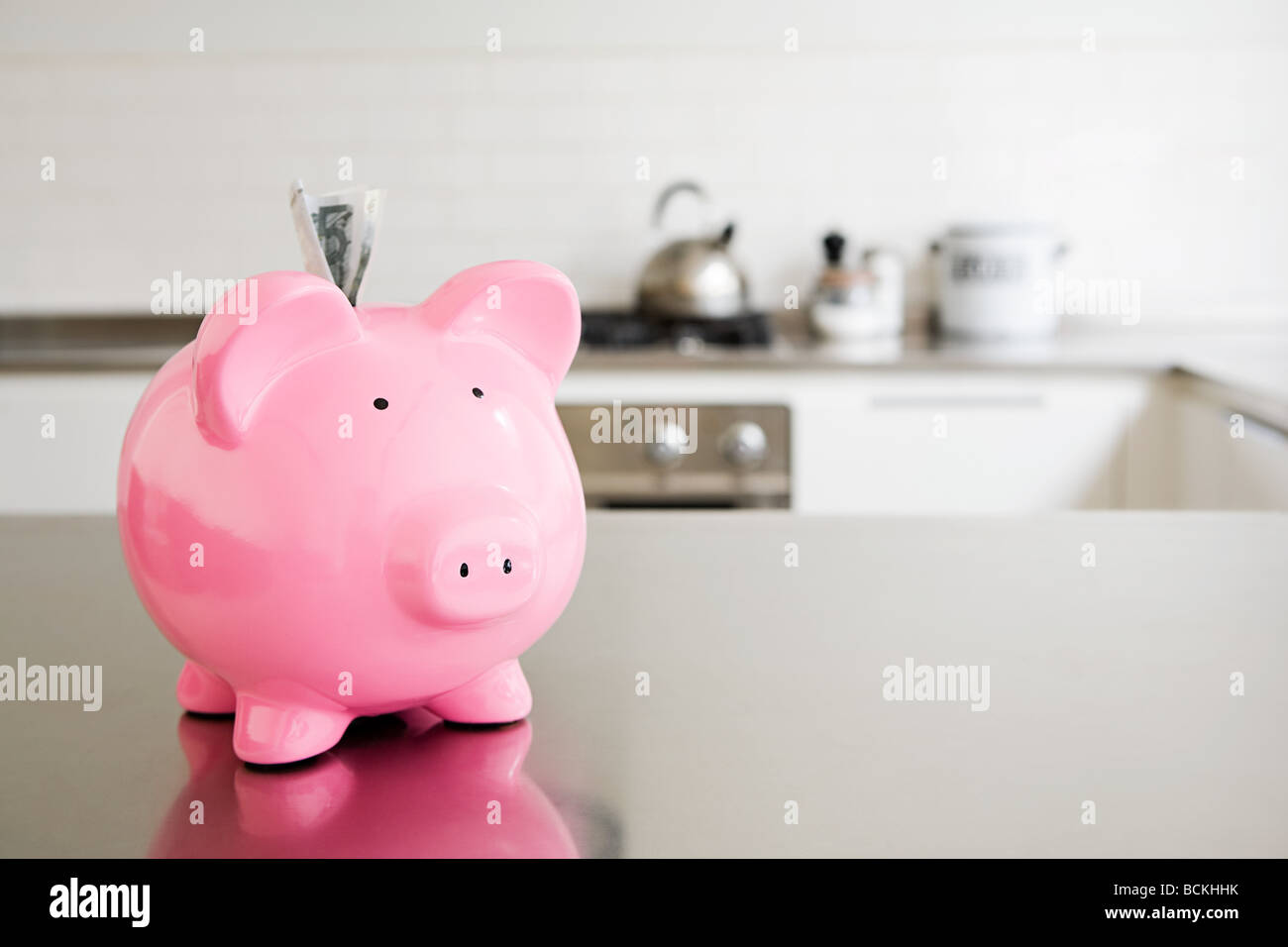 Piggy bank with money in slot - Stock Image