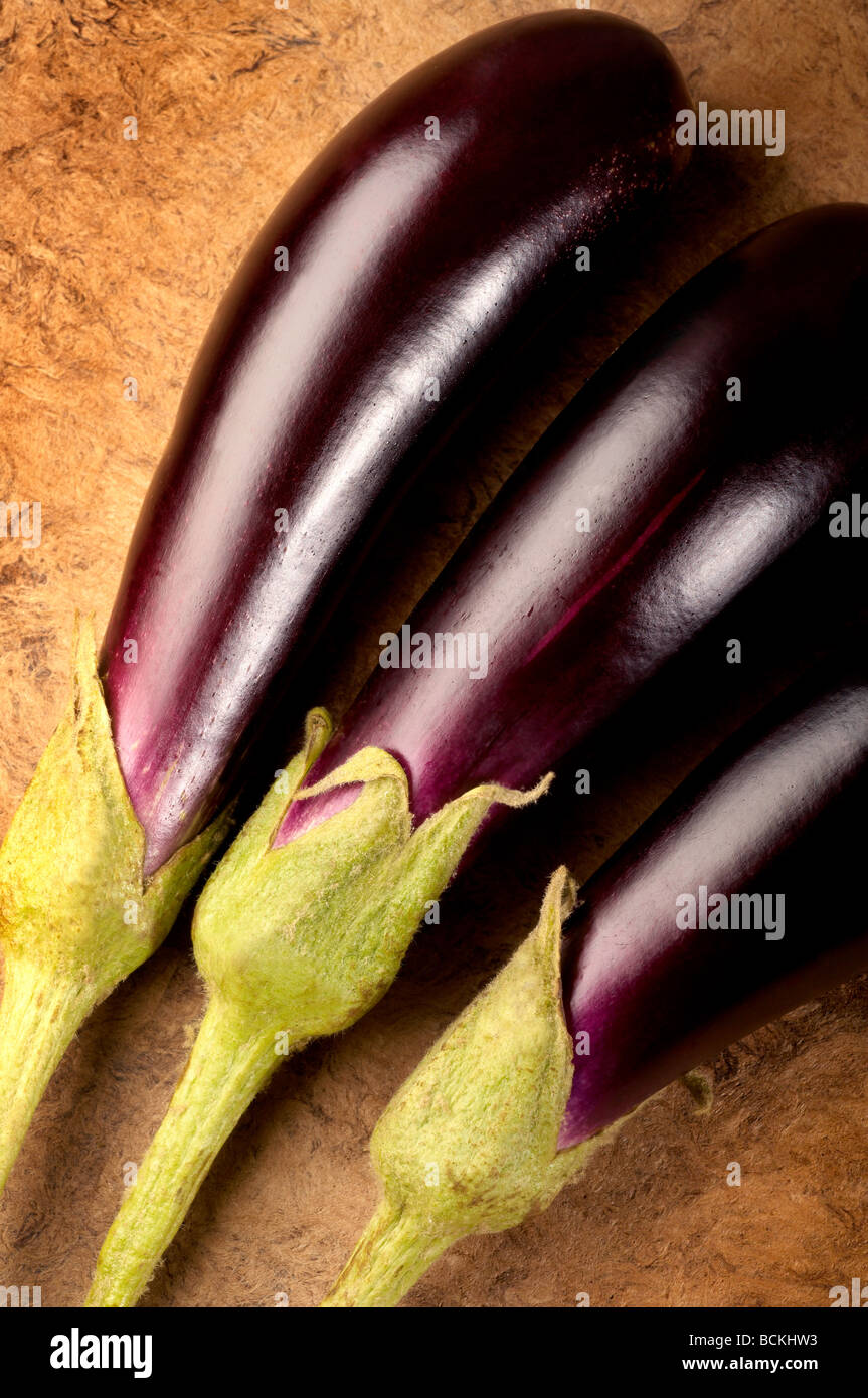 Three Aubergine on textured background - Stock Image