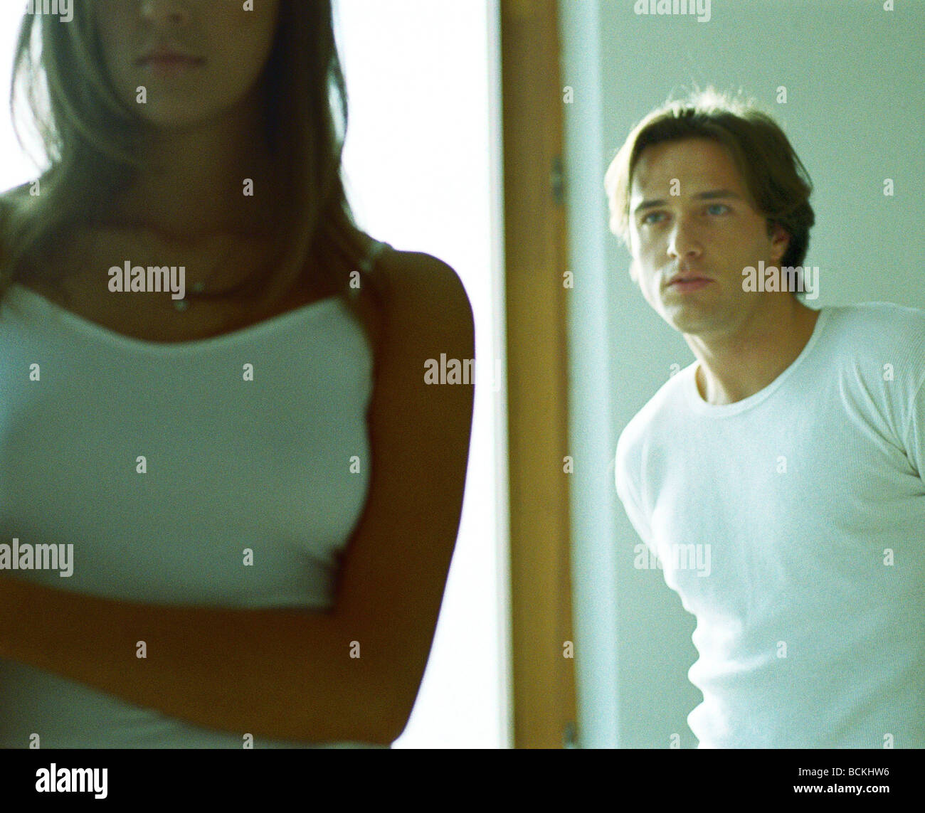 Couple standing apart, man looking at woman - Stock Image