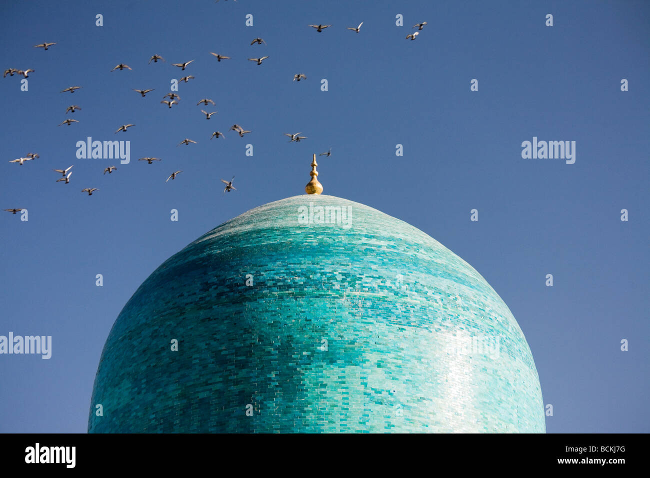 Flock of birds flying over cupola of mosque - Stock Image