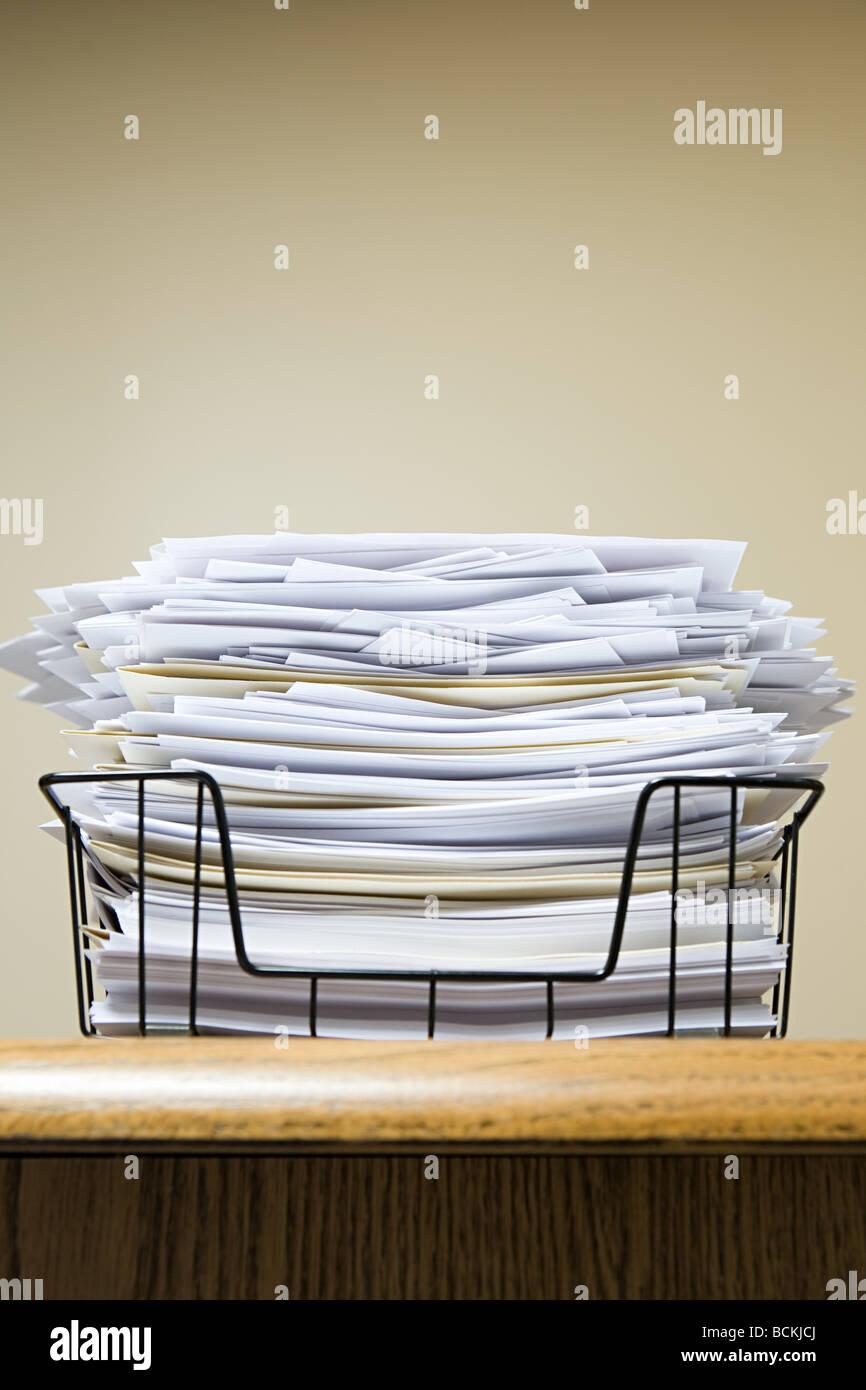 Overflowing paper inbox - Stock Image