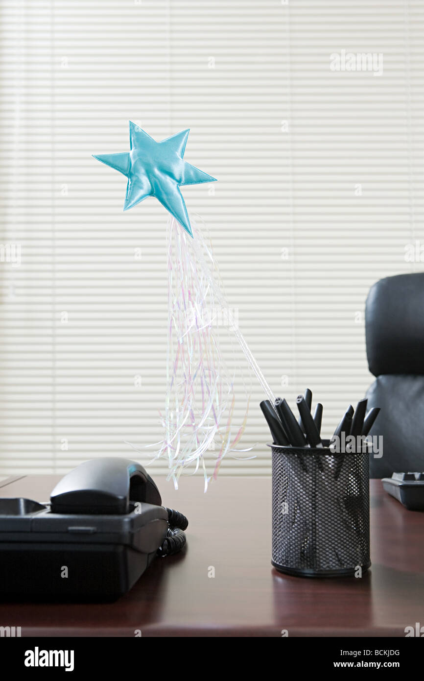Magic wand sticking out of pen holder on office desk - Stock Image