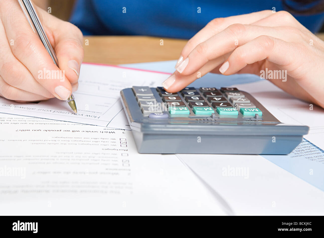Person with calculator and forms - Stock Image