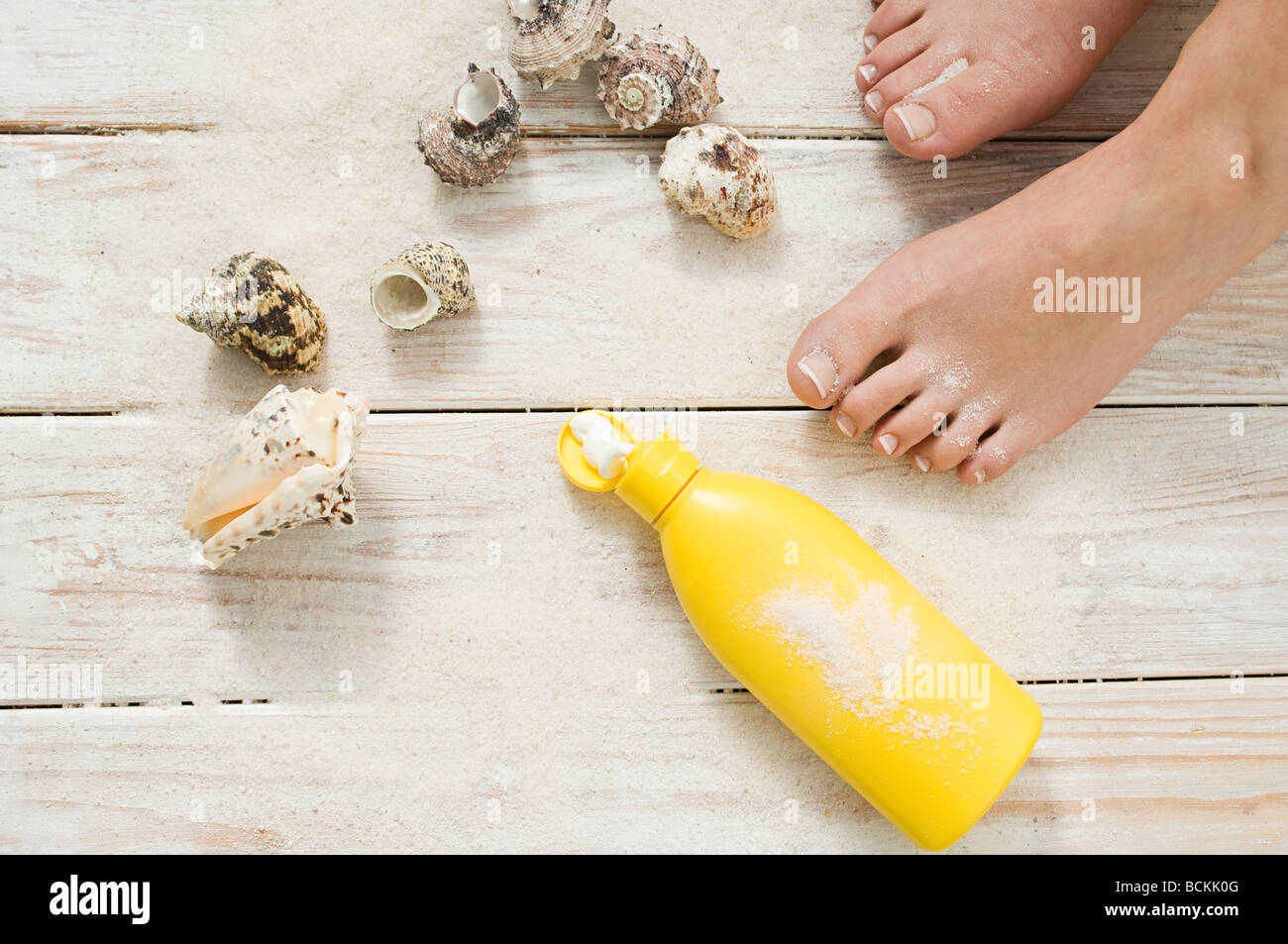 Female feet with shells and suncream - Stock Image