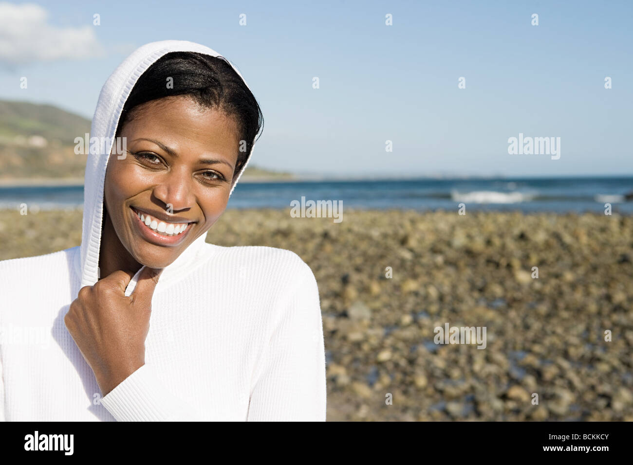 Smiling woman on a shingle beach - Stock Image