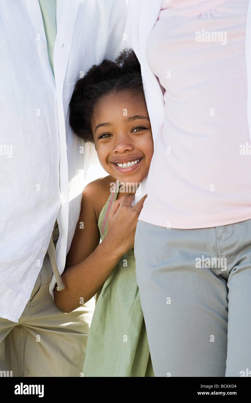Girl standing between her parents - Stock Image