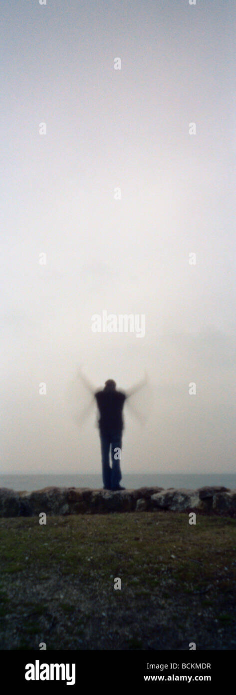 Person silhouetted in front of seascape, flapping arms, vertical - Stock Image