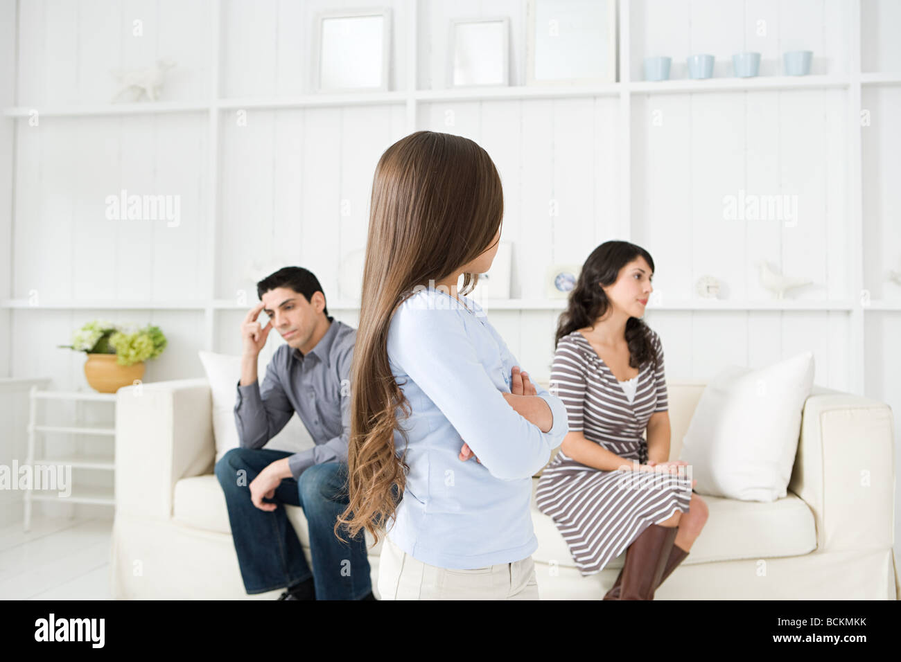 Girl looking at her hostile parents Stock Photo