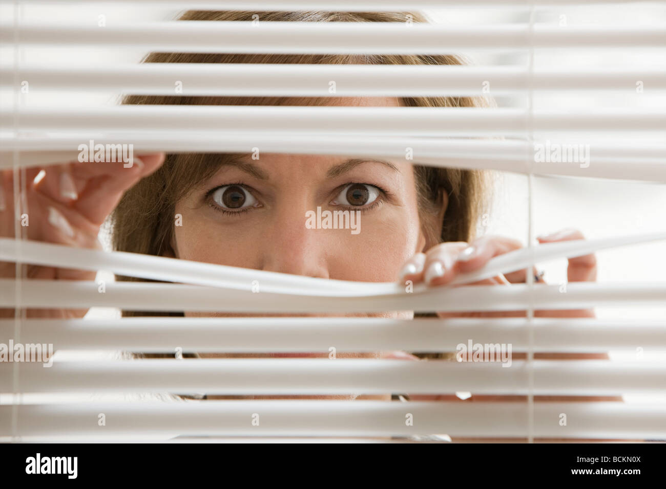 Businesswoman looking through blinds - Stock Image