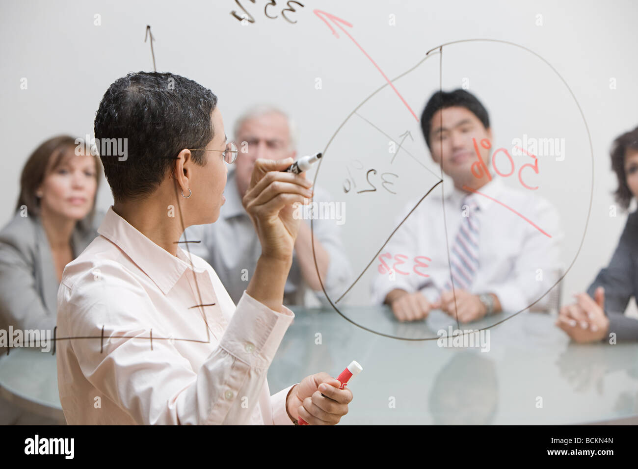Businesswoman with chart on glass - Stock Image