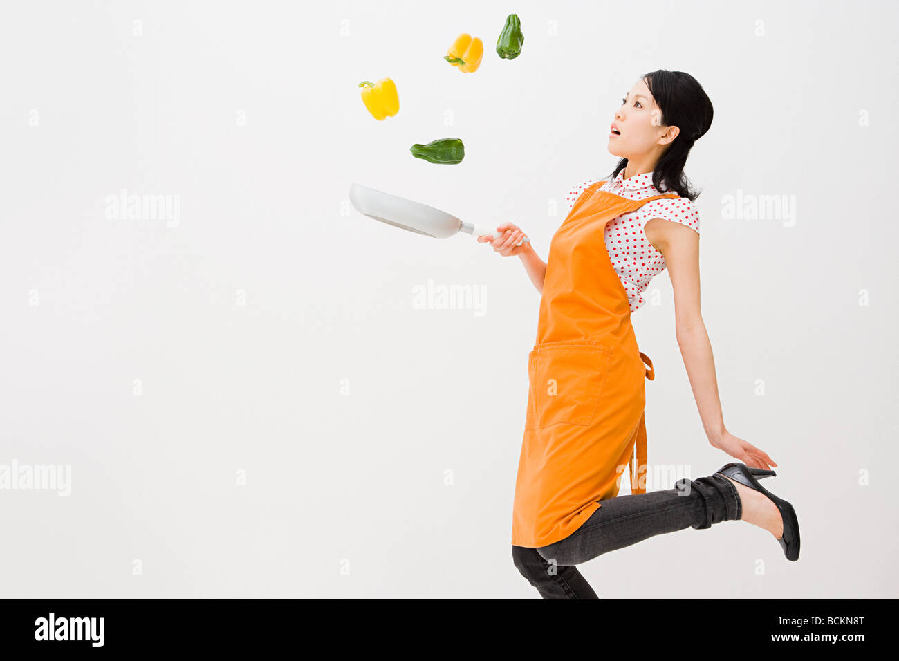 Woman tossing peppers - Stock Image
