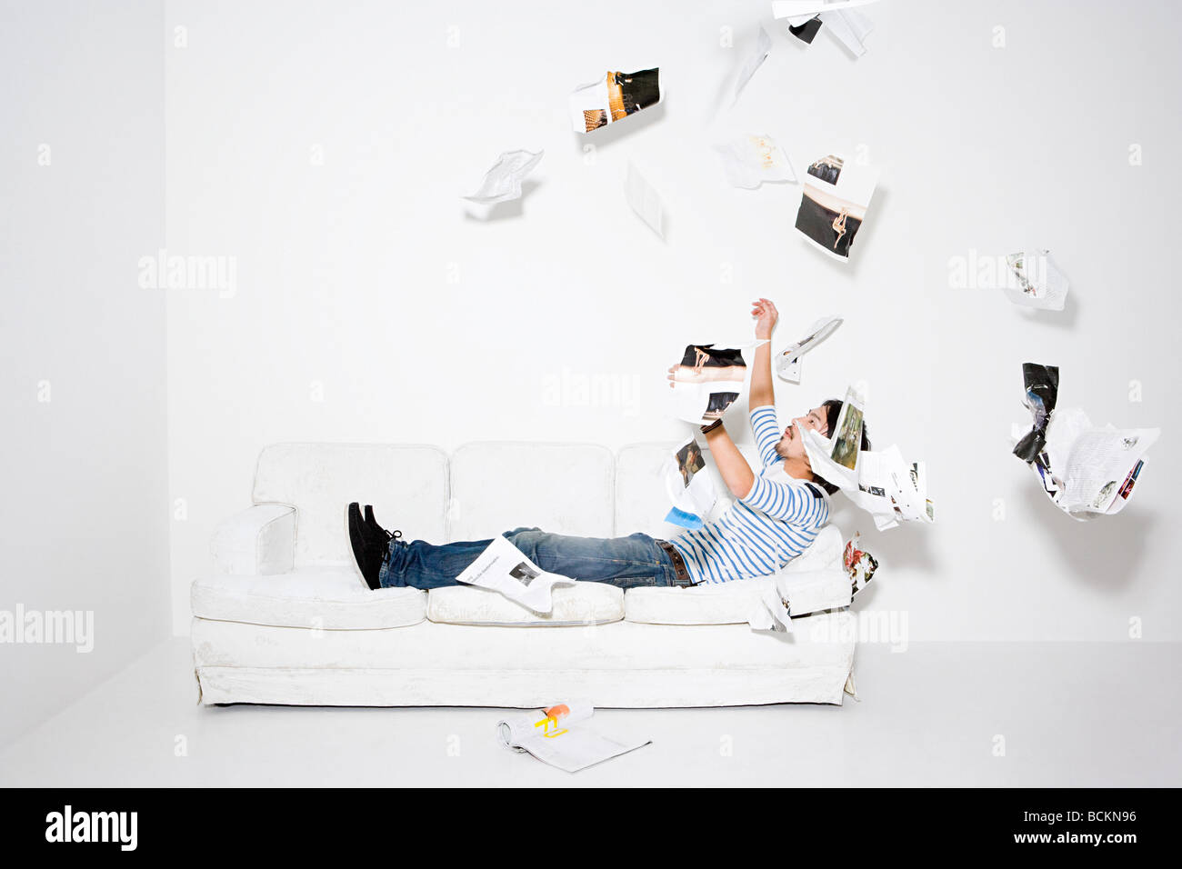 Man throwing pages of a magazine - Stock Image