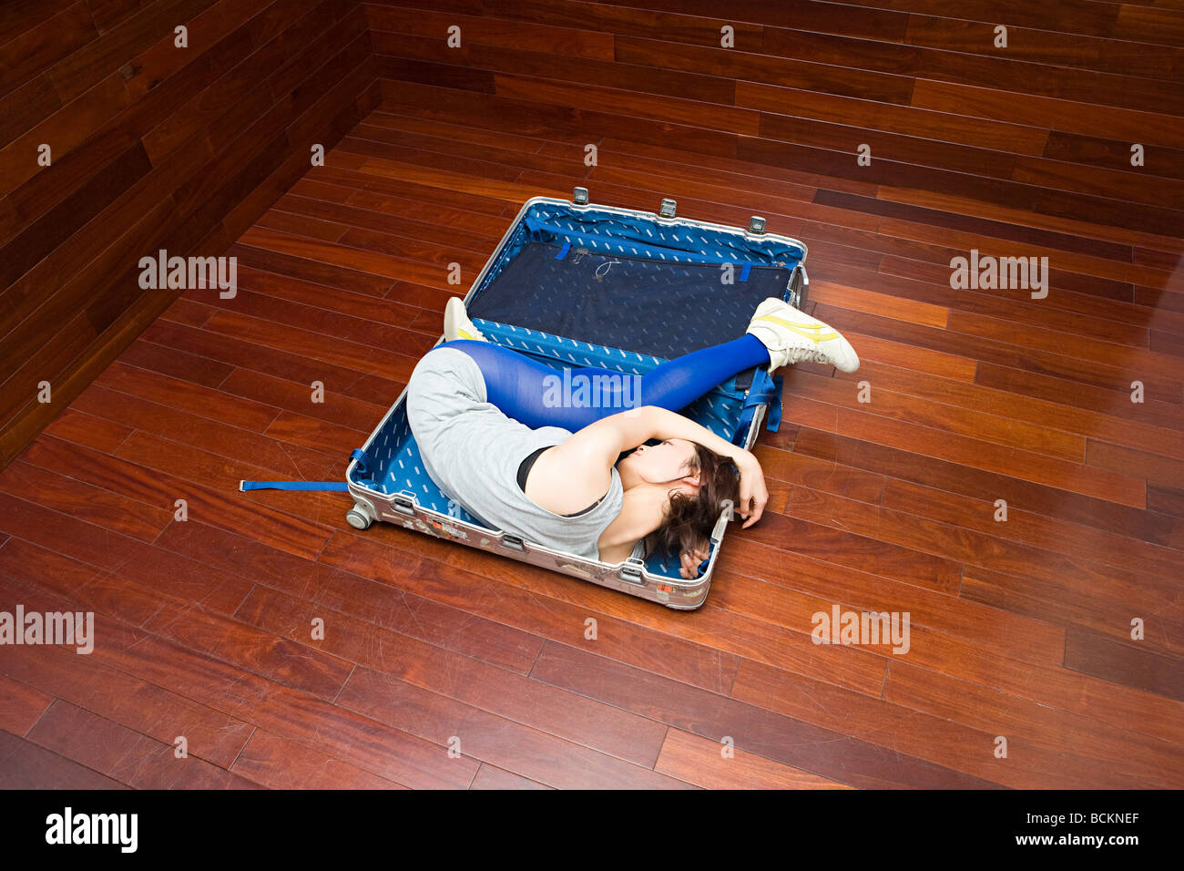 Young woman in a suitcase - Stock Image