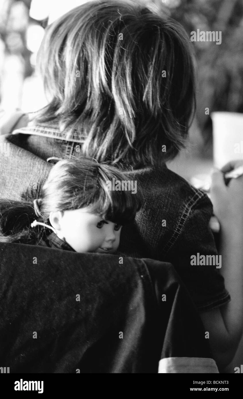 Child with doll in backpack, rear view, b&w - Stock Image