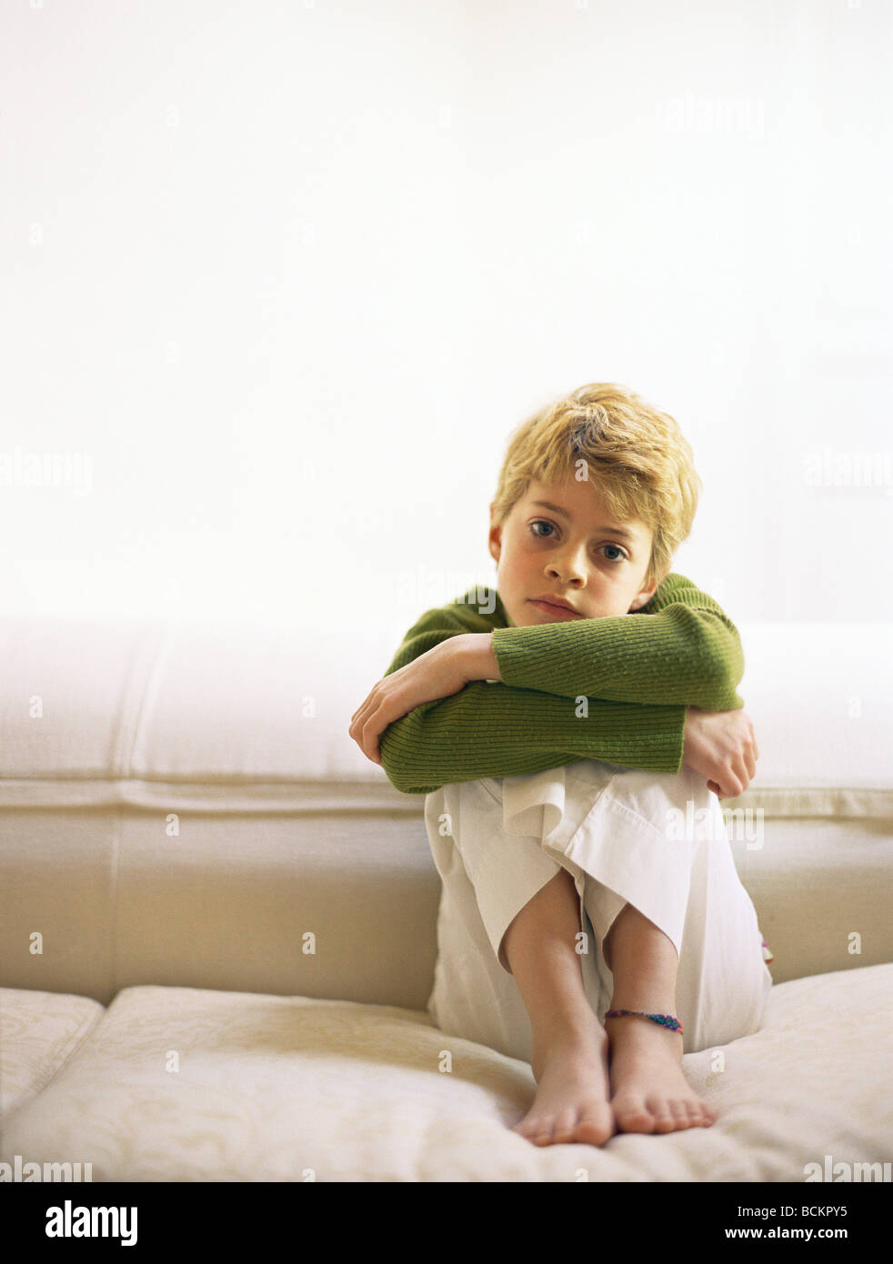 Girl Sitting On Sofa With Knees Up And Arms Folded Stock Photo