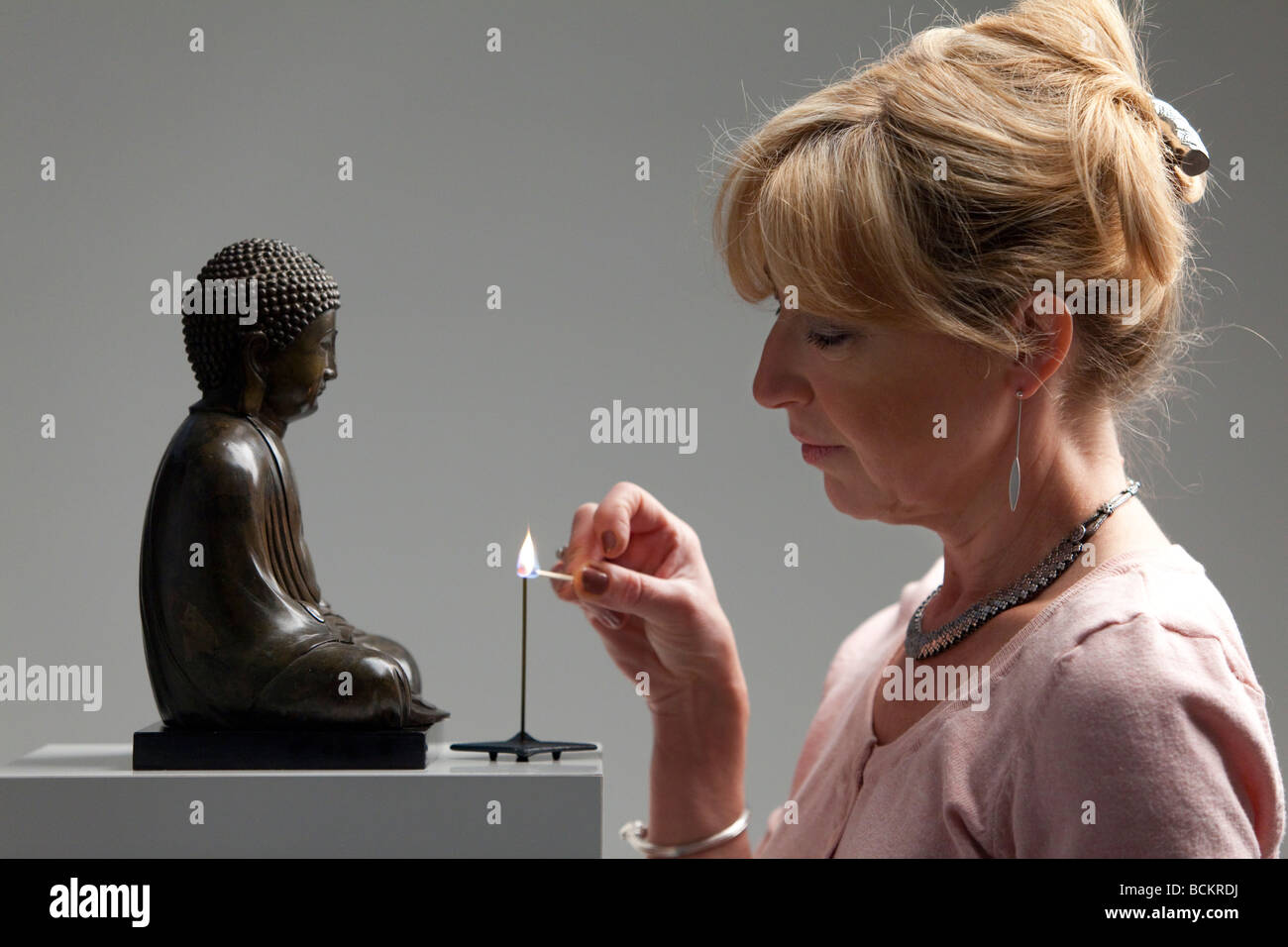 Senior woman lightens incense in front of a buddha - Stock Image