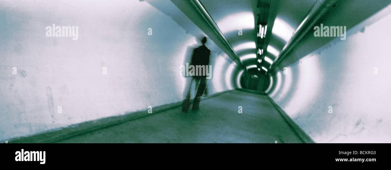 Man walking in underground walkway, panoramic view - Stock Image