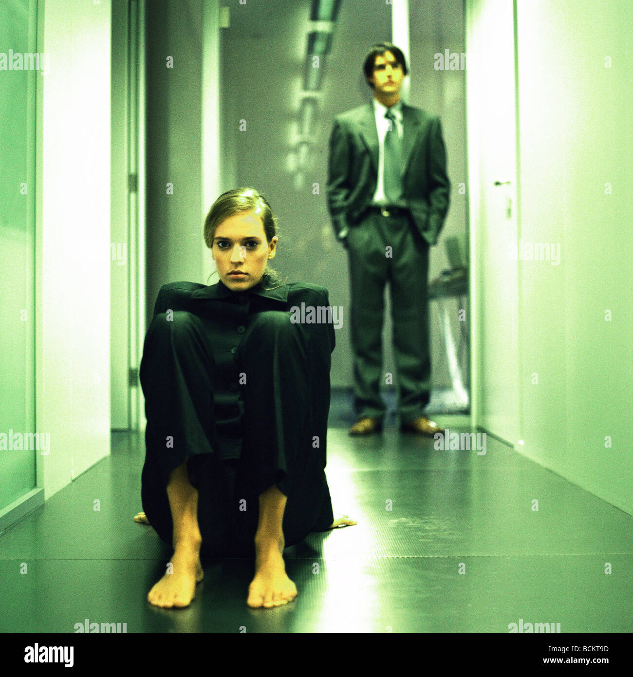 Woman sitting on floor in hallway, man standing behind - Stock Image
