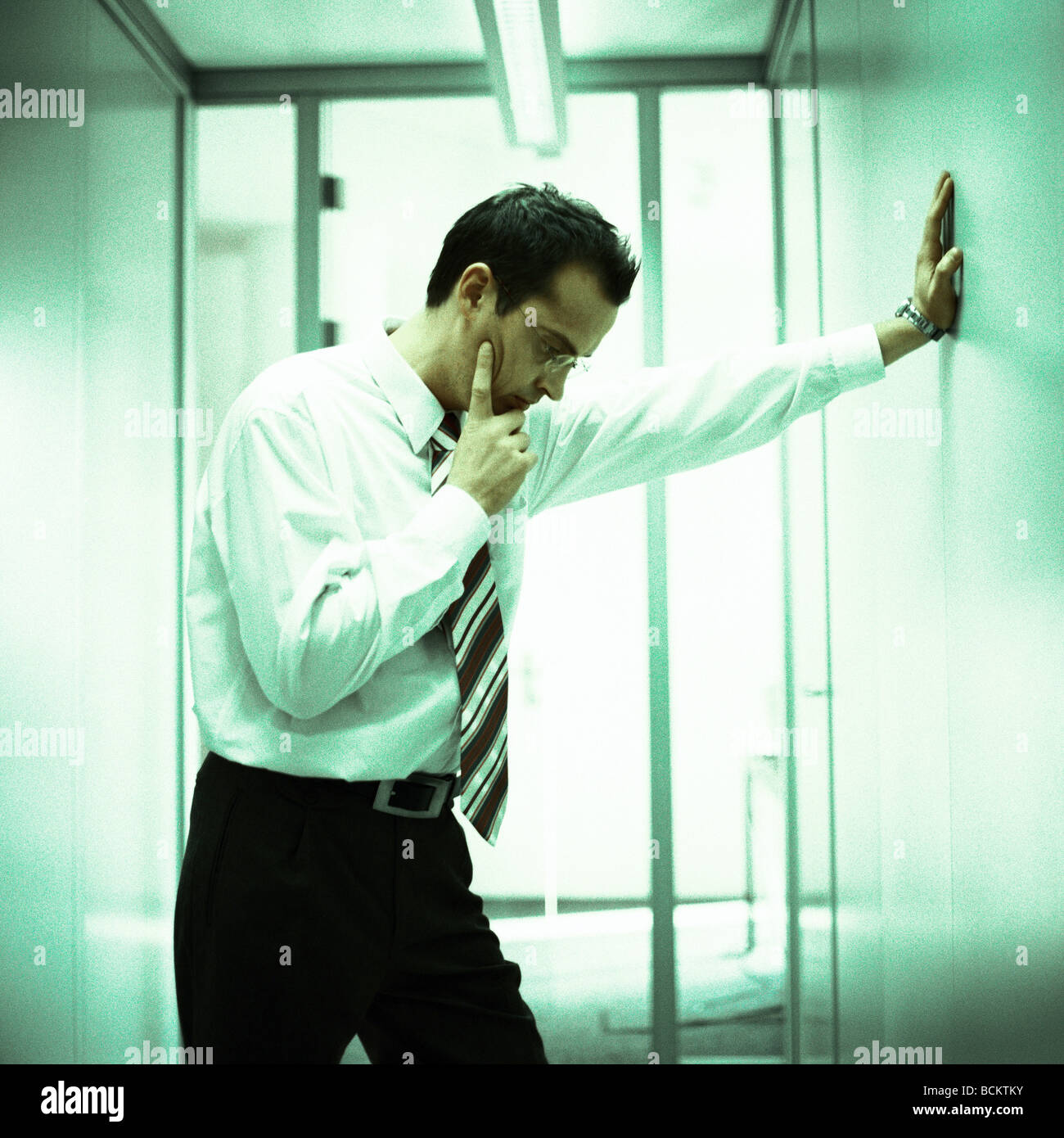 Businessman Standing Leaning Hand On Wall Stock Photo
