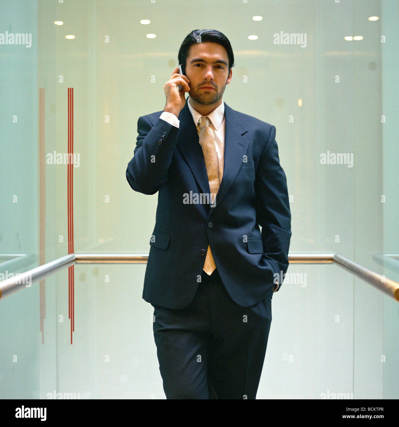 Businessman standing with cellphone in elevator Stock Photo