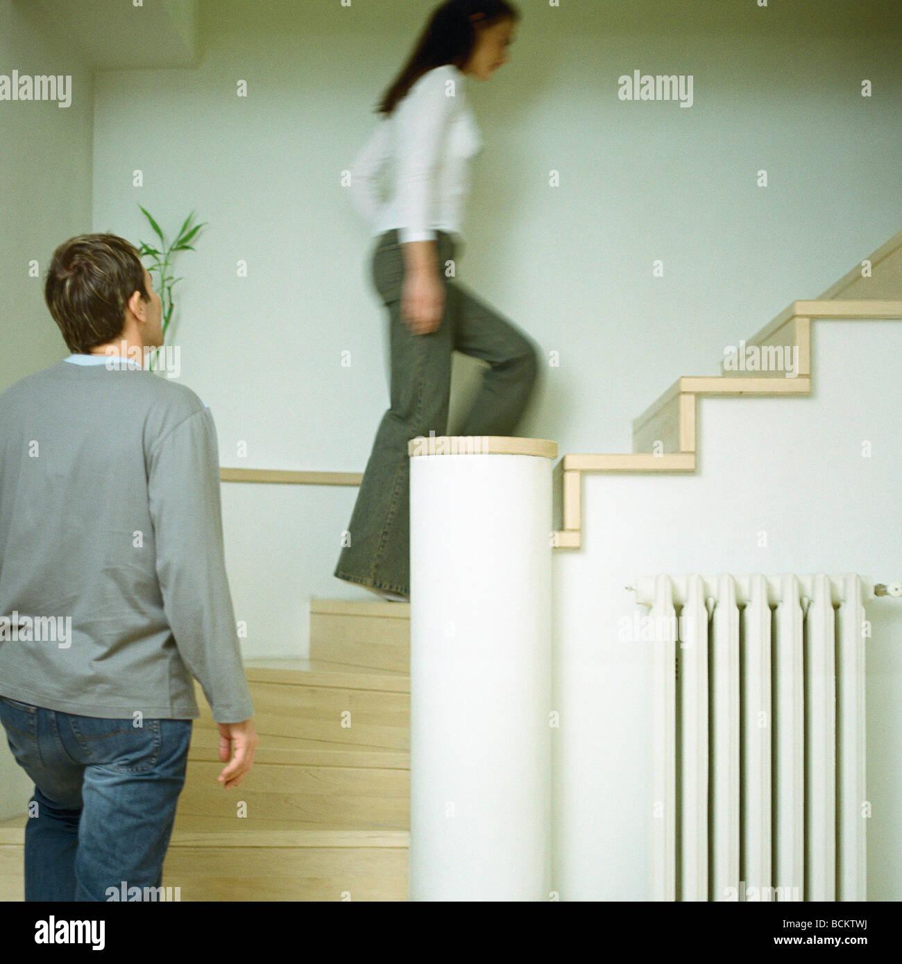 Man and woman walking up steps, interior - Stock Image