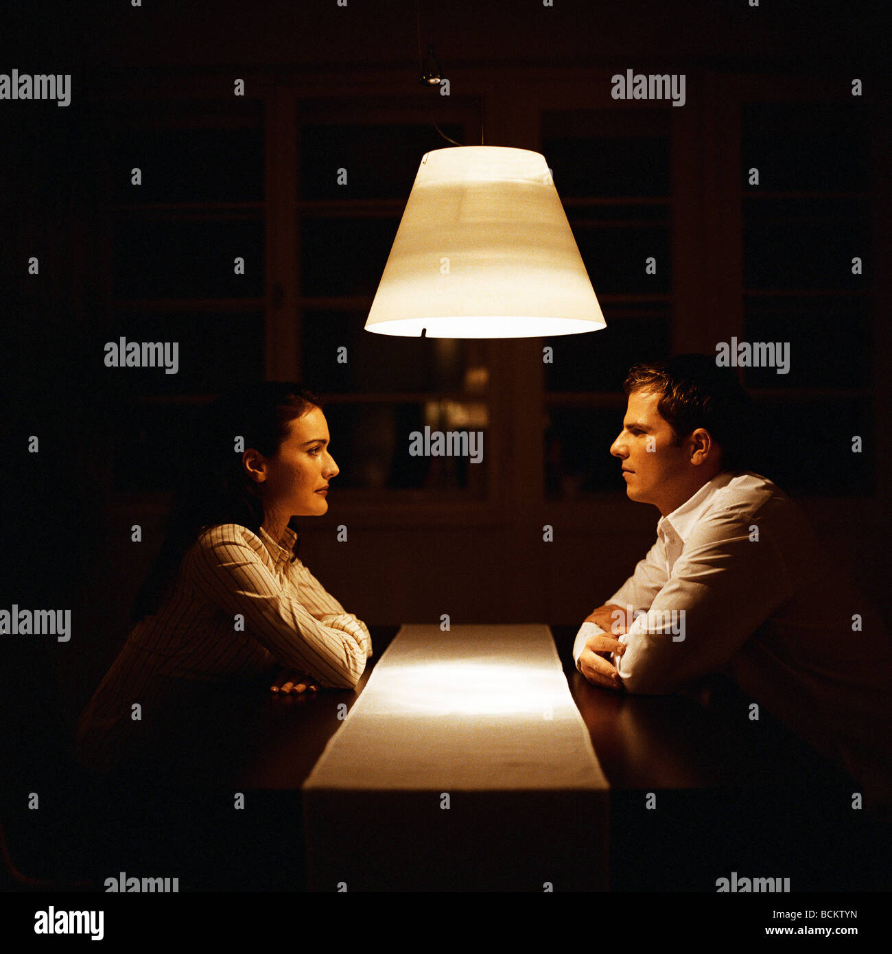 Man and woman face to face at table - Stock Image