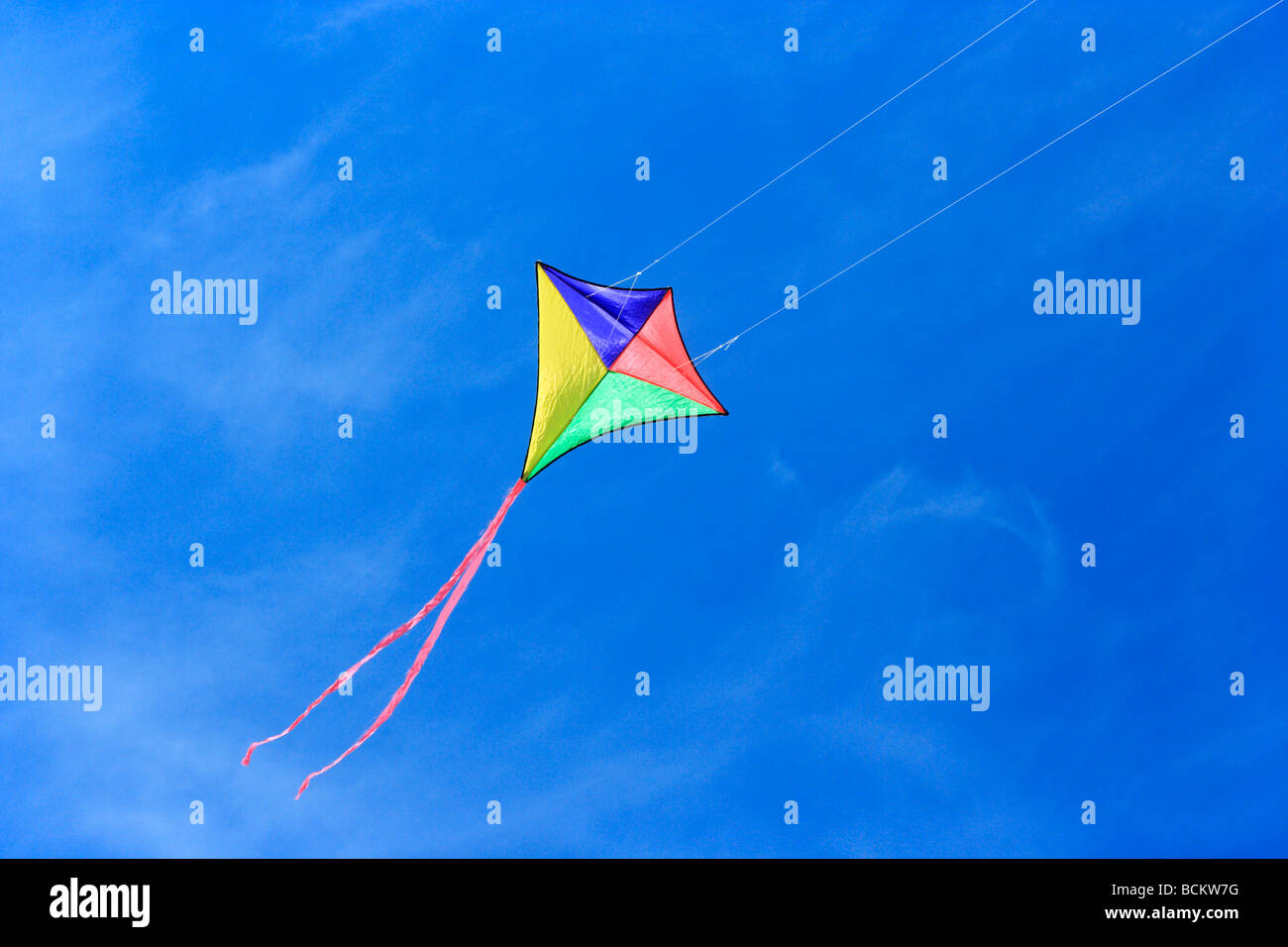Colourful kite on a blue sky - Stock Image