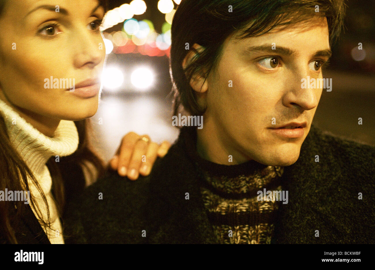 Woman with hand on man's shoulder at night, close-up - Stock Image