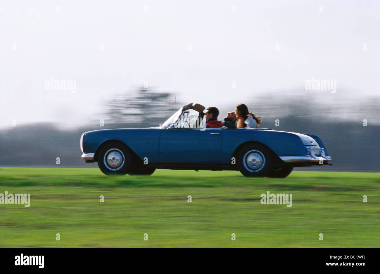 People riding in convertible car - Stock Image