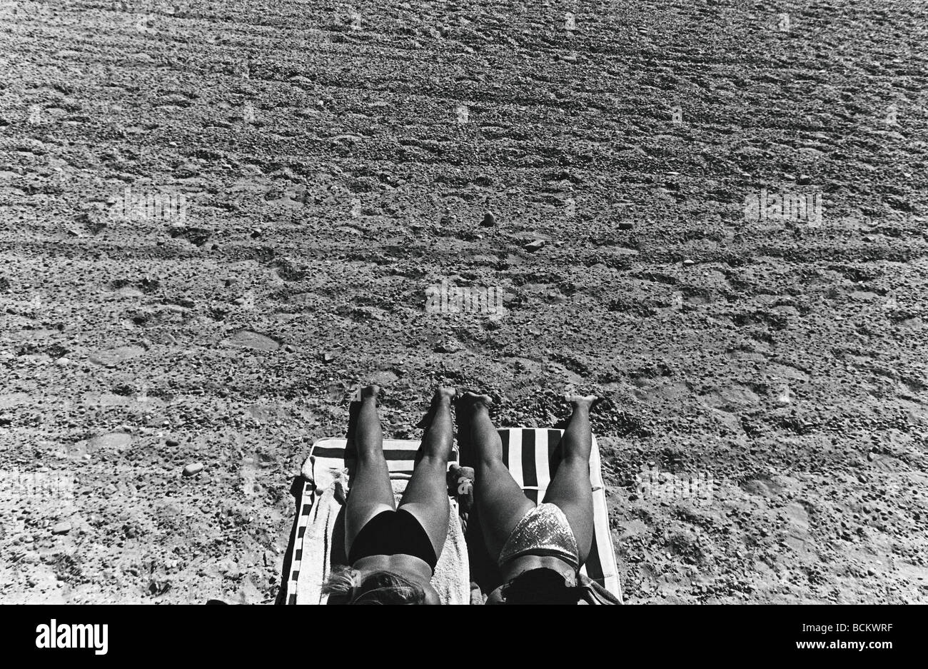 Two women sunbathing, lower section, high angle view, b&w - Stock Image