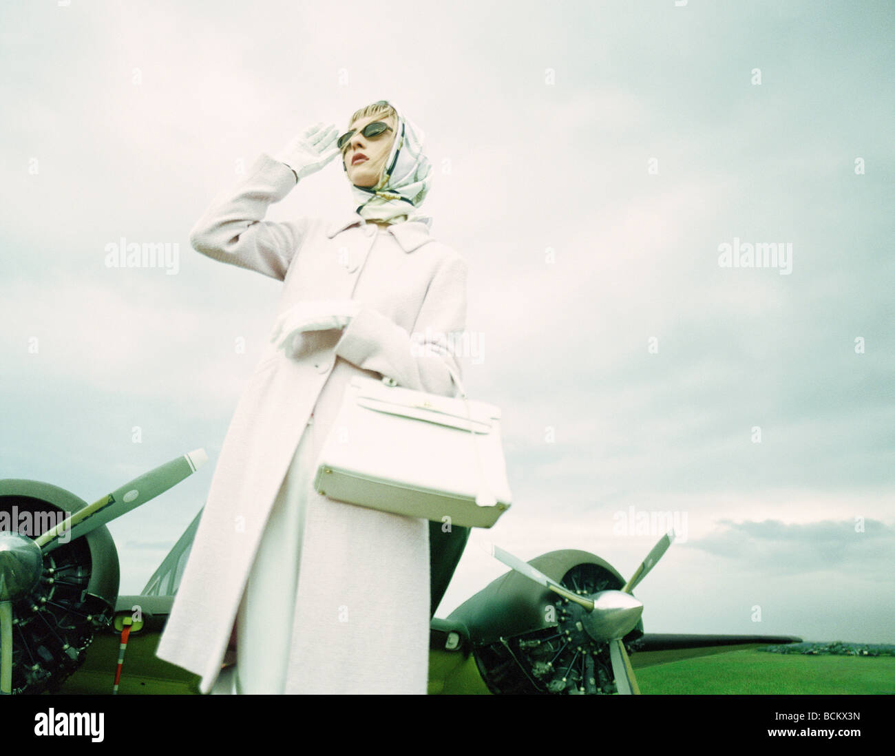 Woman standing in front of airplane, low angle view - Stock Image