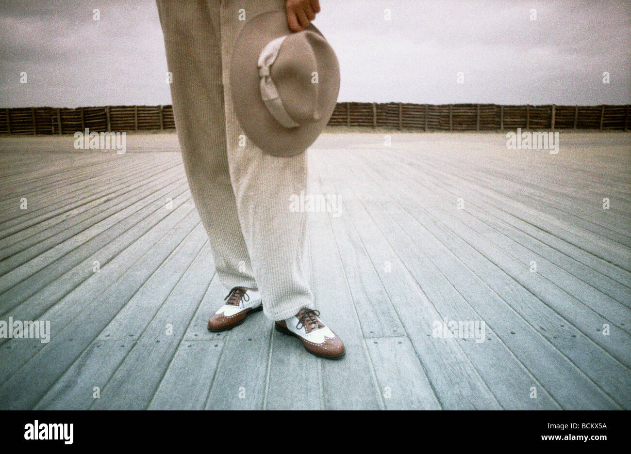 Person standing on wooden planks, holding hat - Stock Image