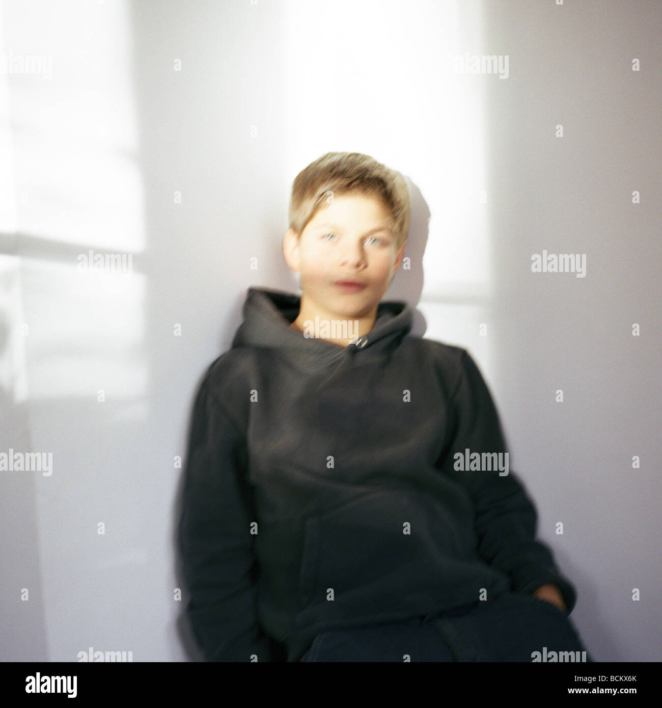 Boy leaning against wall with shadows - Stock Image