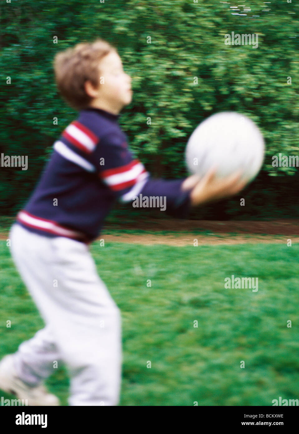 Child Catching Ball Blurred Side View Stock Photo