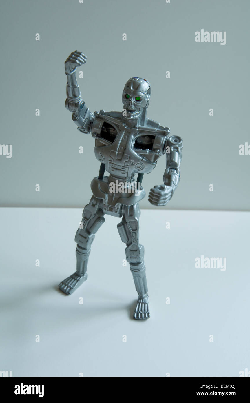 A robot mechanical man looking angry with raised fist and bright green jealous eyes. - Stock Image