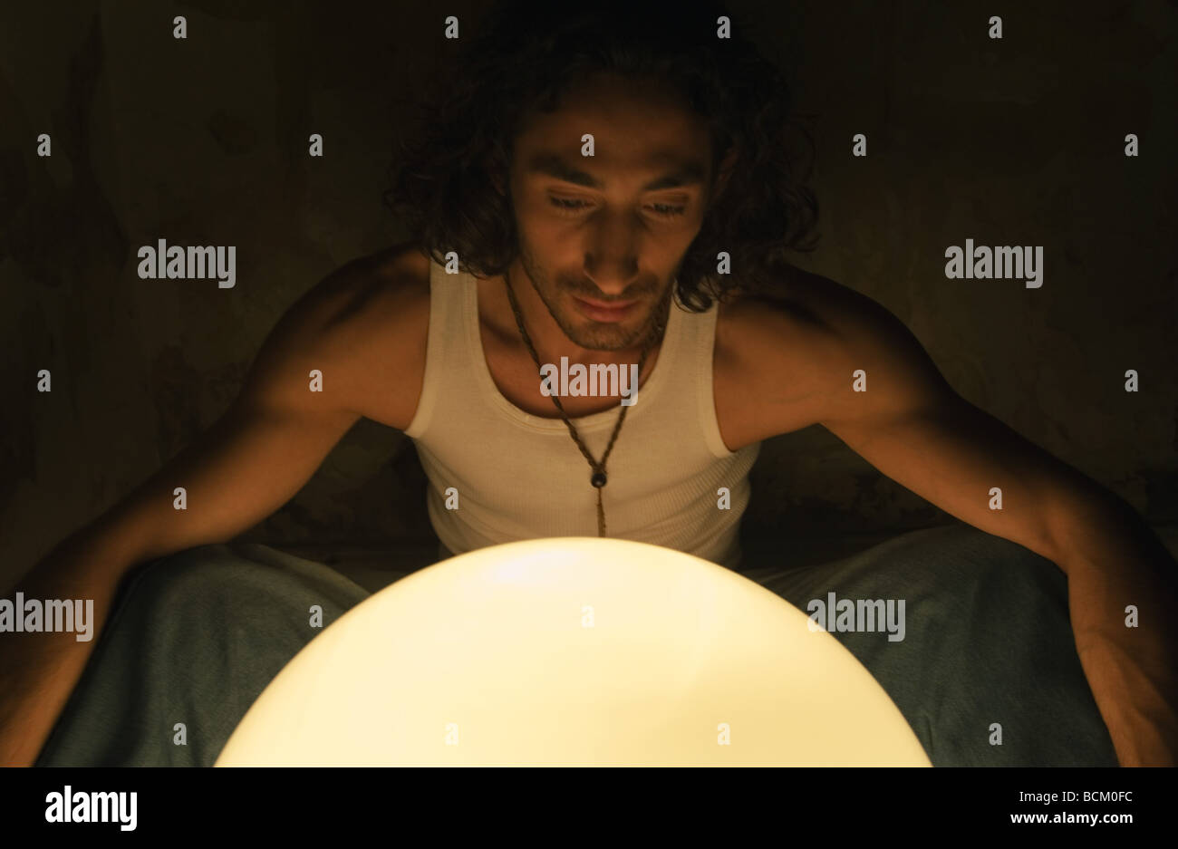 Man looking at glowing orb - Stock Image
