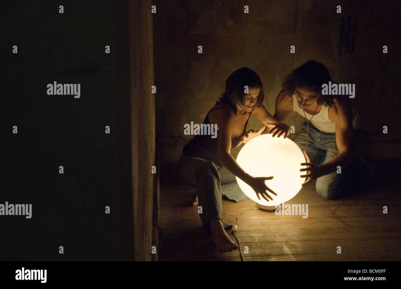 Woman and man touching glowing orb - Stock Image