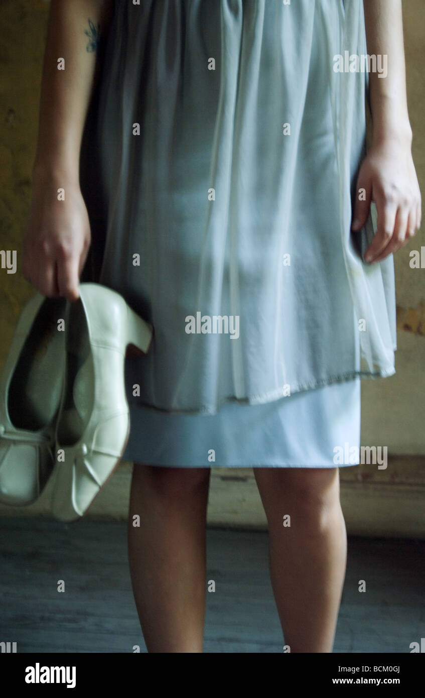 Woman in dress, holding pair of shoes by side, cropped, front view - Stock Image