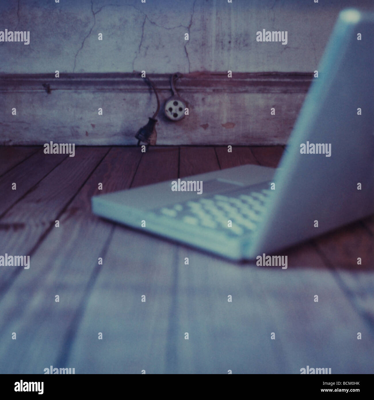 Laptop on hardwood floor - Stock Image