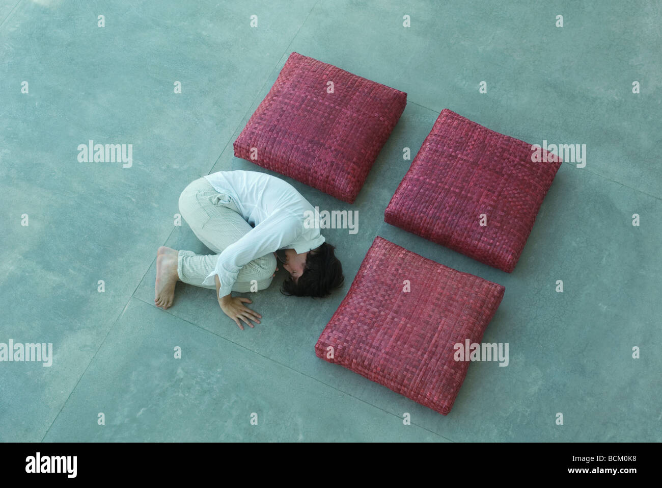 Three square cushions and man arranged in square shape, man lying in fetal position, high angle view - Stock Image