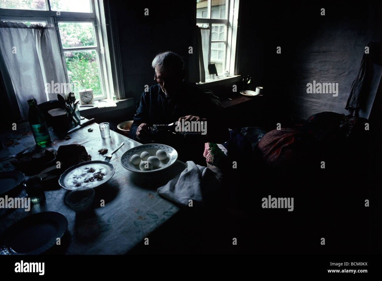 Ivan Greeb pours a glass of Vodka as he has a last breakfast in his home in Dorogin near Chernobyl station, Ukraine. - Stock Image