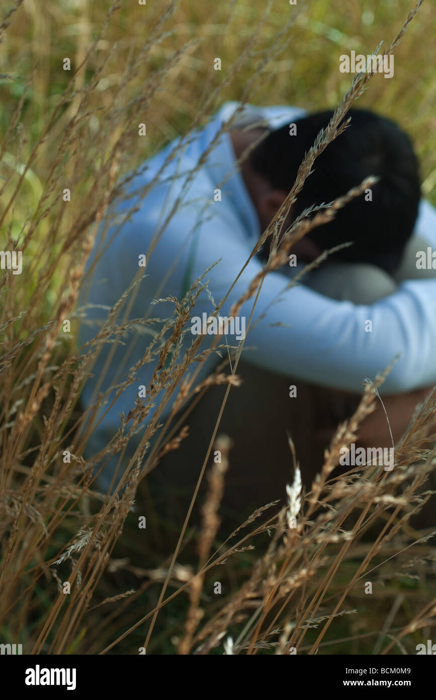 Man sitting in field with head on knees, focus on long grass in foreground Stock Photo