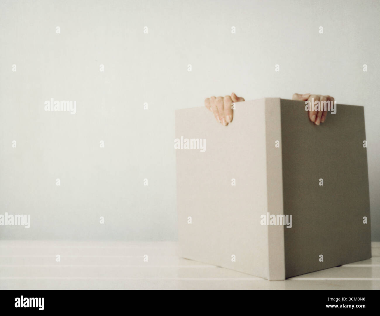 Woman behind open book, hand's holding top of book, close-up - Stock Image