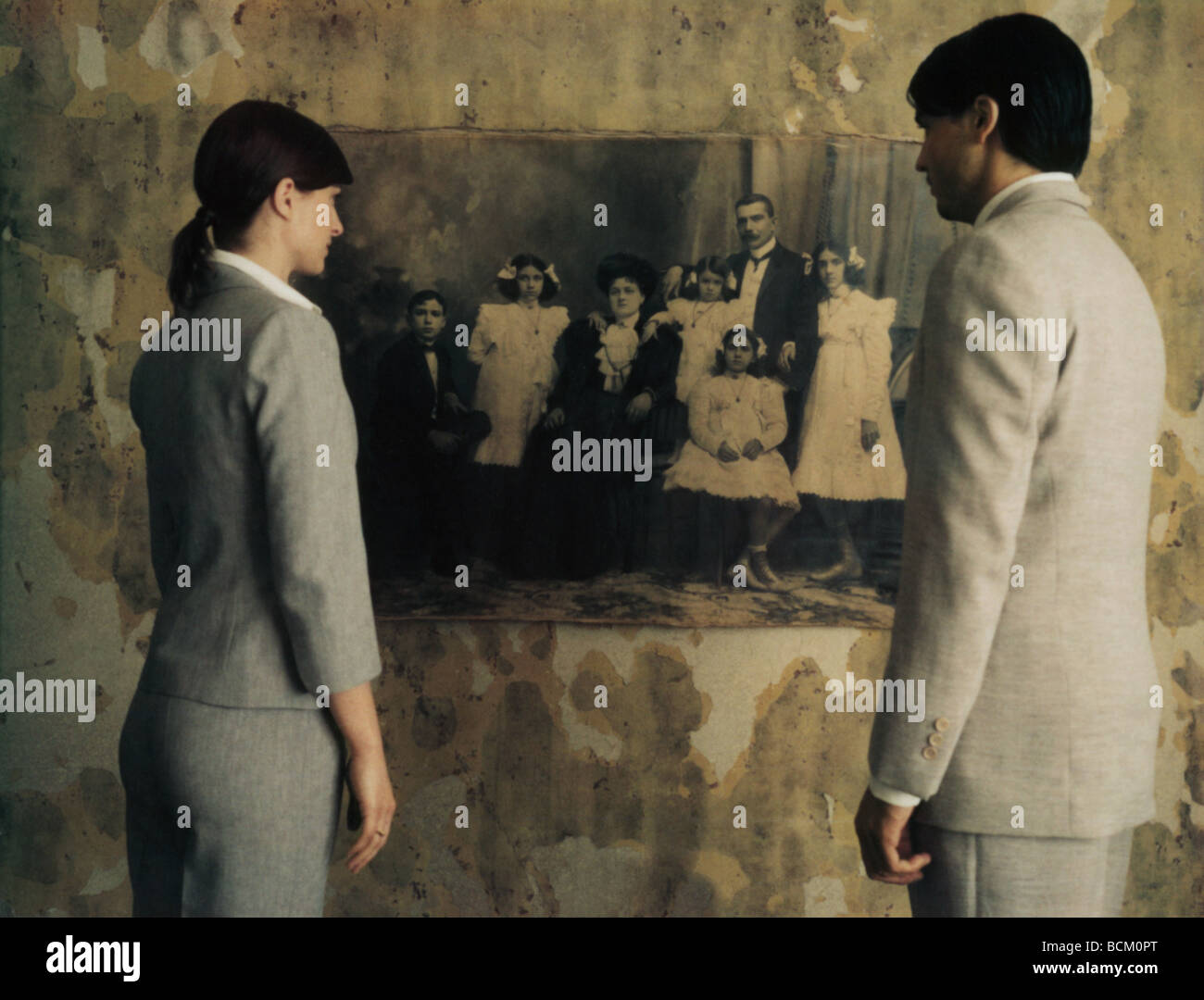 Man and woman standing side by side, looking at black and white photo on wall, rear view - Stock Image