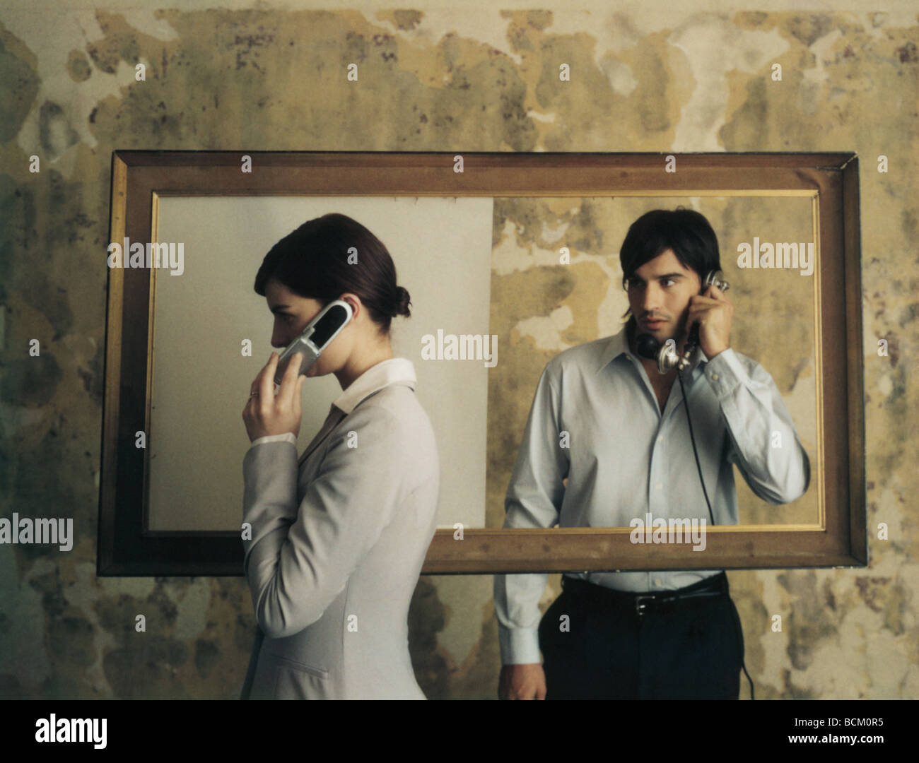 Standing on either side of picture frame, woman using cell phone while man using old-fashioned landline phone watches - Stock Image