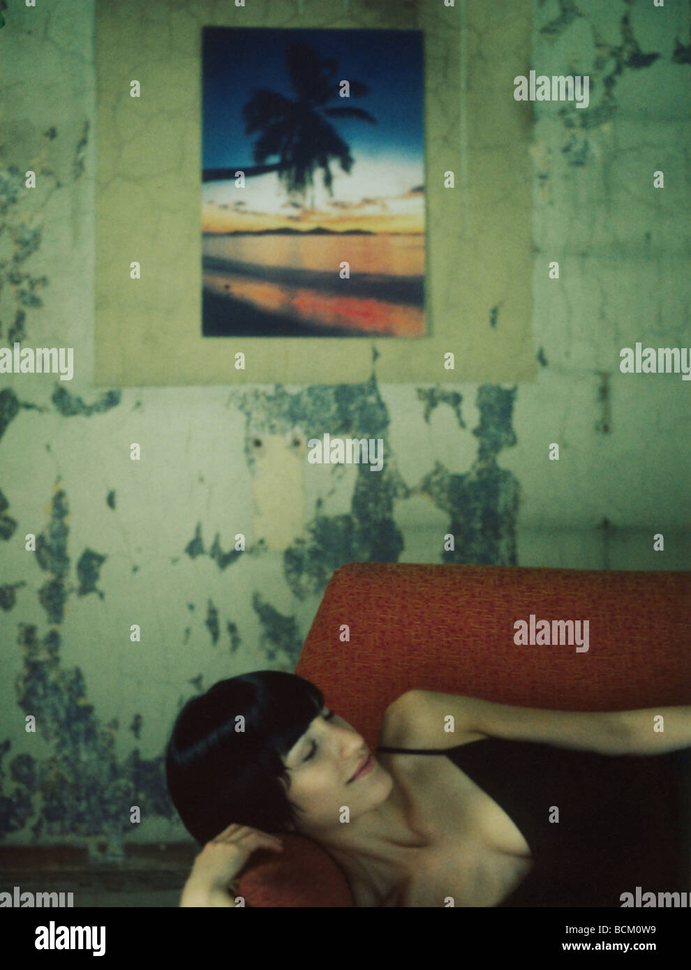 Woman lying on sofa with eyes closed, smiling, color photo on wall in background - Stock Image