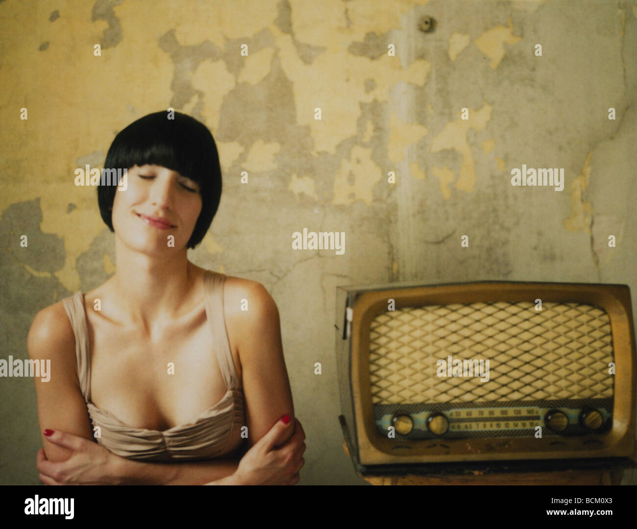 Woman sitting next to old-fashioned radio, arms folded and eyes closed - Stock Image