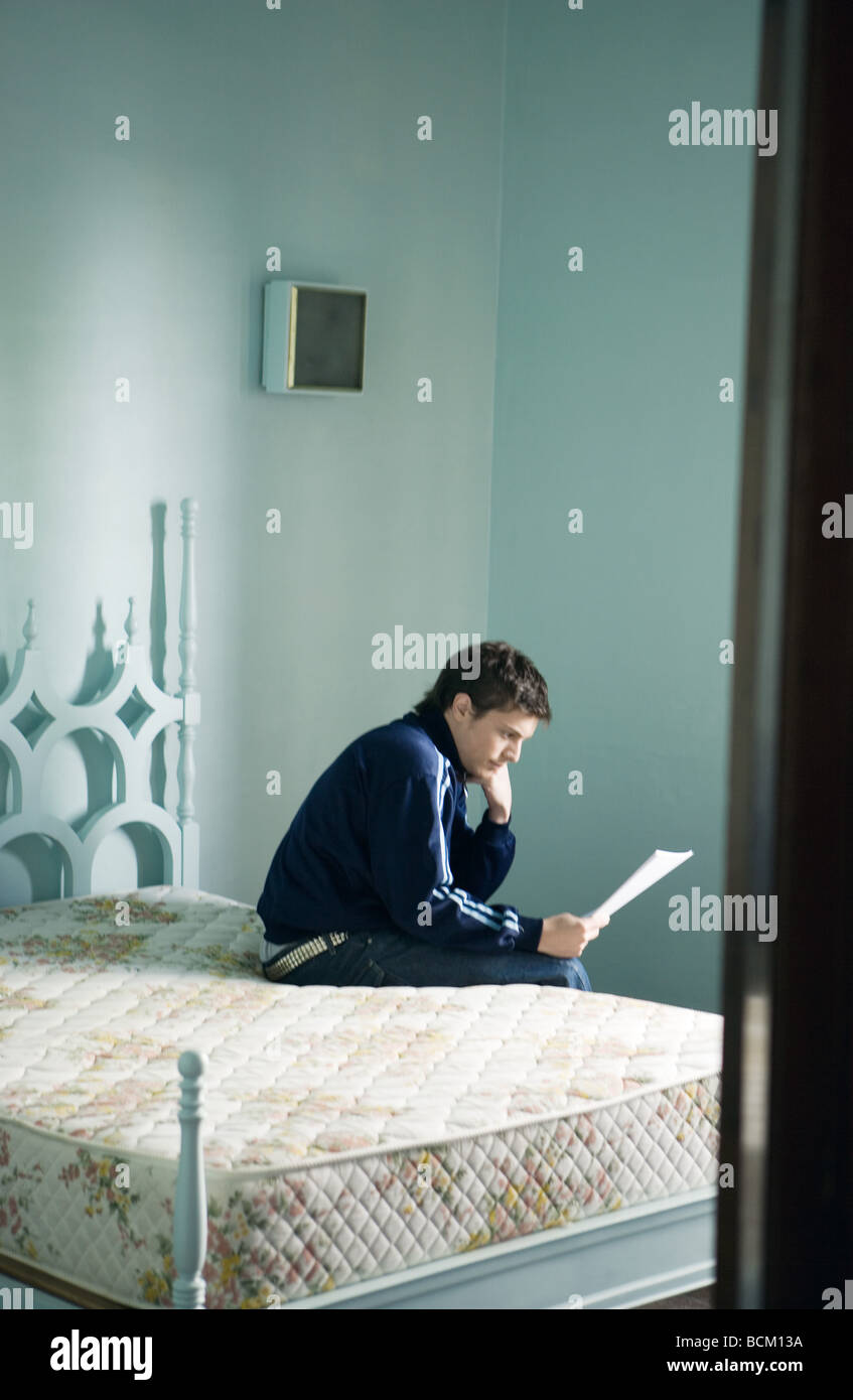 Young man sitting on edge of bed, reading document - Stock Image