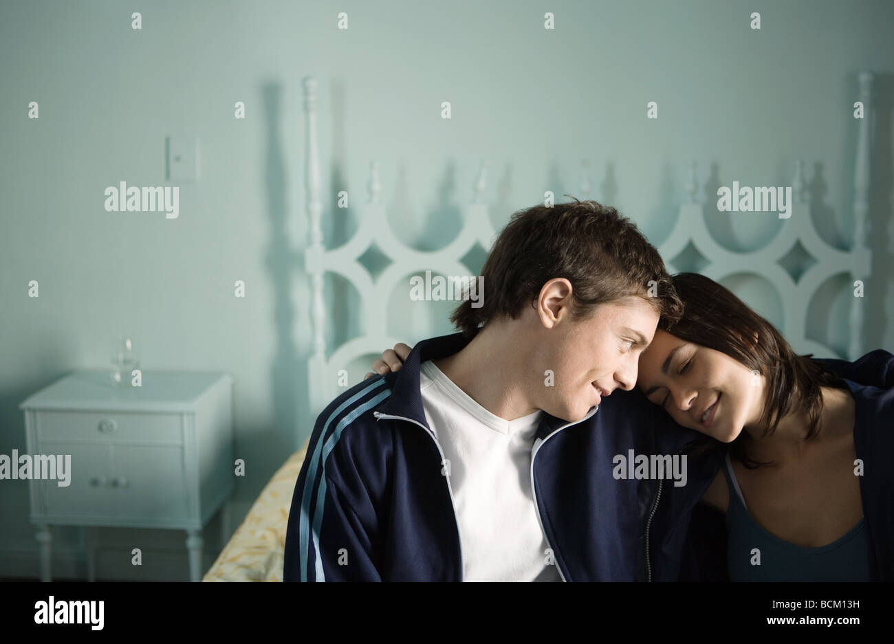Young couple sitting on edge of bed with heads together - Stock Image